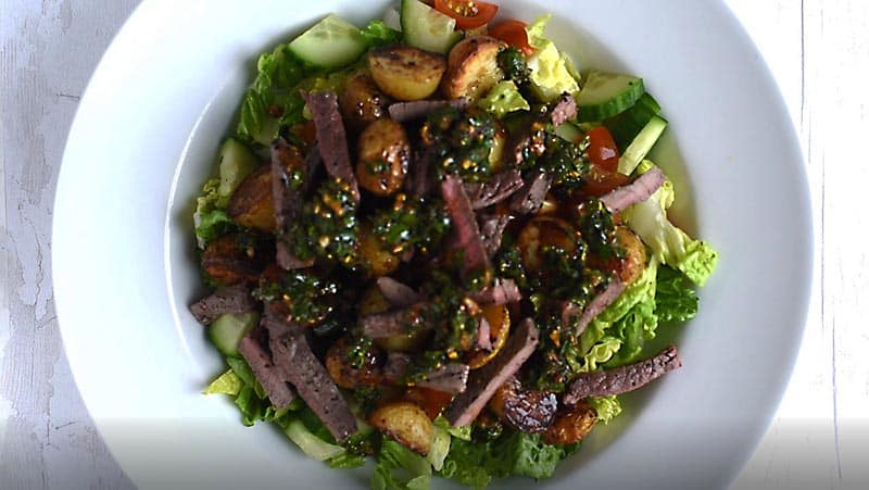 A bowl of steak salad with chermoula drizzled over it