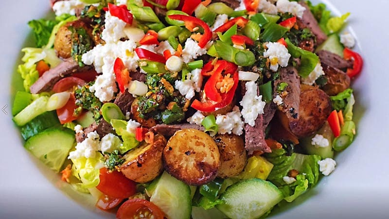 Steak salad topped with red chillies and feta