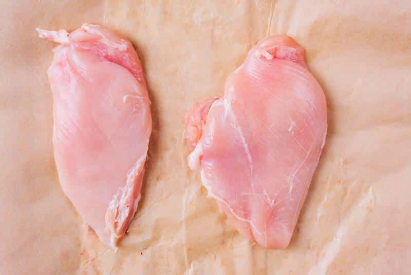 Two flattened chicken breasts on baking paper