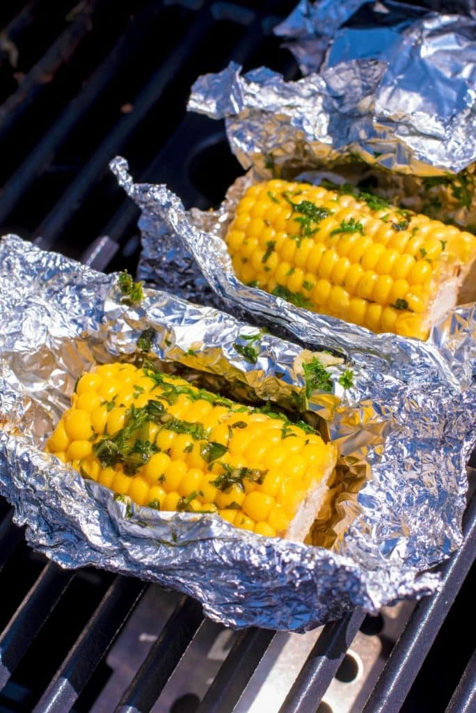 Corn wrapped in open foil on a barbecue grill
