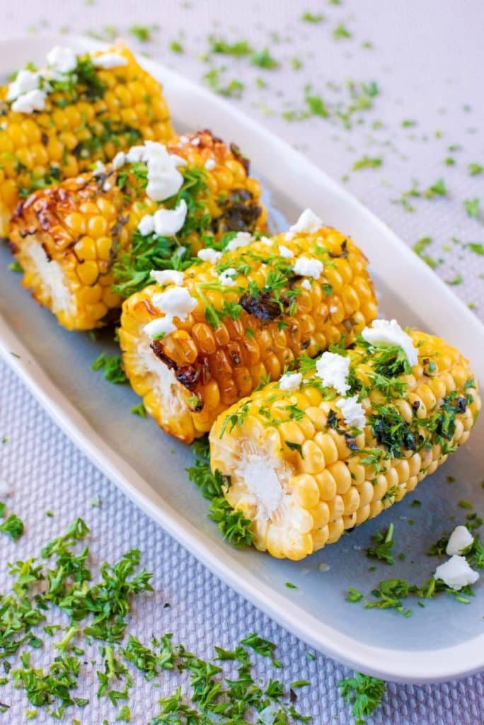 Four corn on the cob with char marks topped with herbs and feta