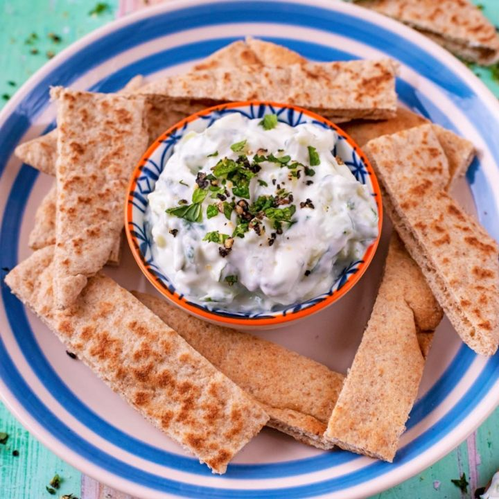 Tzatziki surrounded by sliced pita on a blue and white plate