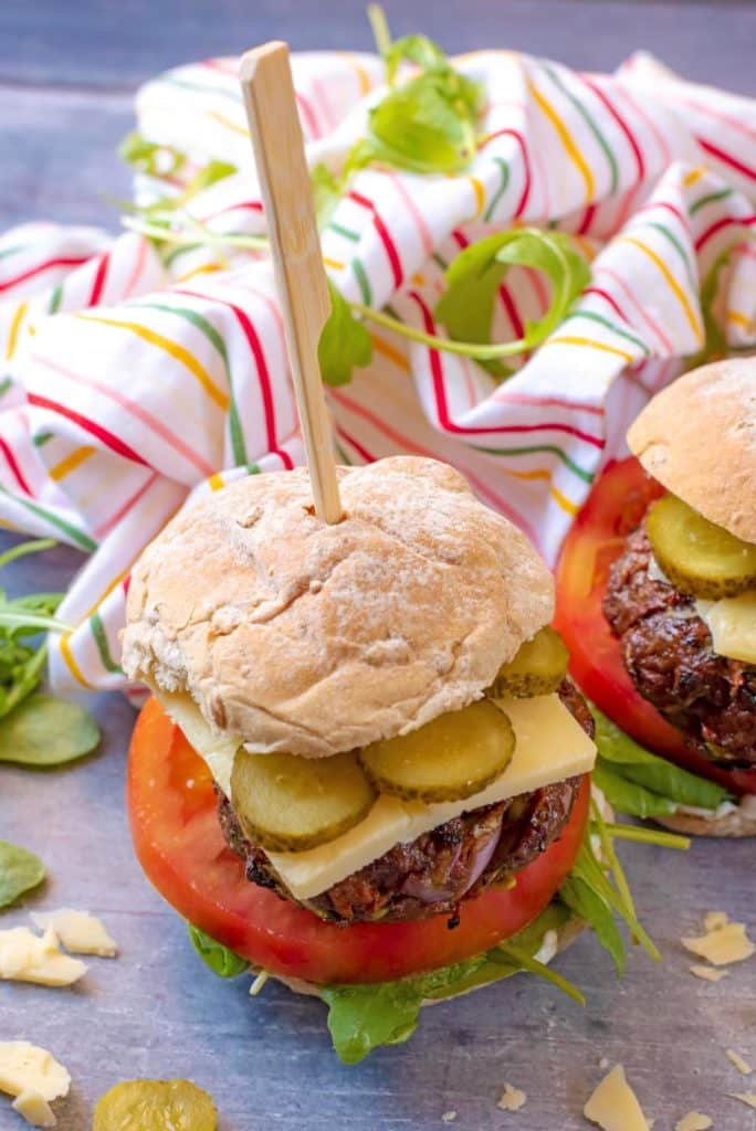 A beef burger in a bun with salad, cheese and pickles. A small wooden skewer is pushed through the whole burger