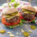 Hidden Vegetable Beef Burgers in buns with cheese, tomato and pickles.