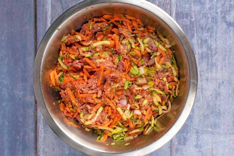 a mixing bowl containing shredded vegetables, herbs, tomato paste and ground beef, all mixed together