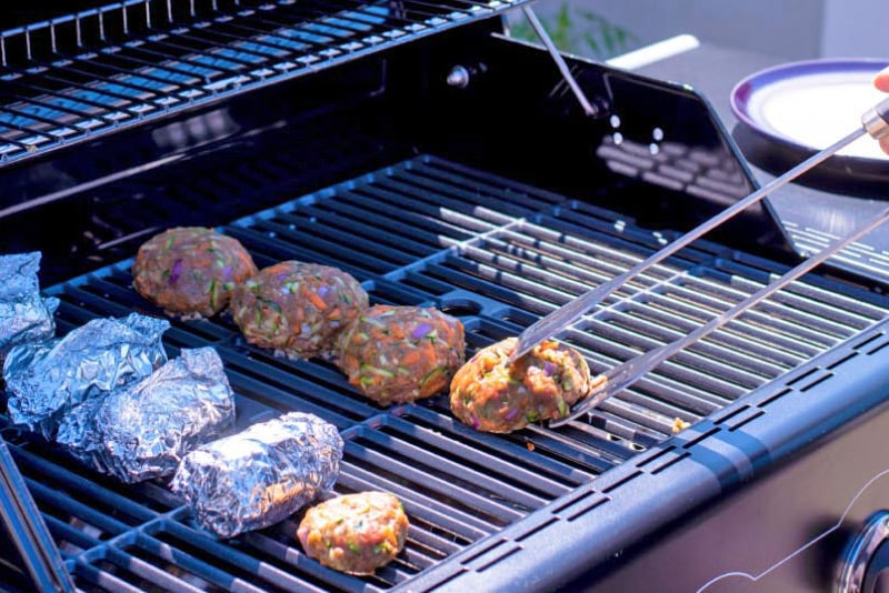 Hidden Vegetable beef burgers cooking on a barbecue