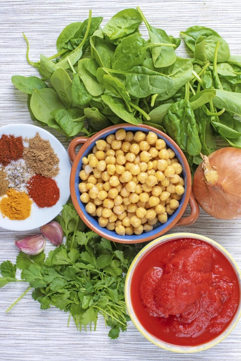 A bowl of chickpeas surrounded by tomatoes, spinach, an onion, herbs and spices