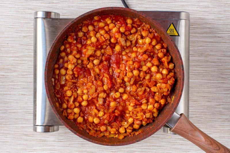 Tomatoes, chickpeas and onions cooking in a frying pan