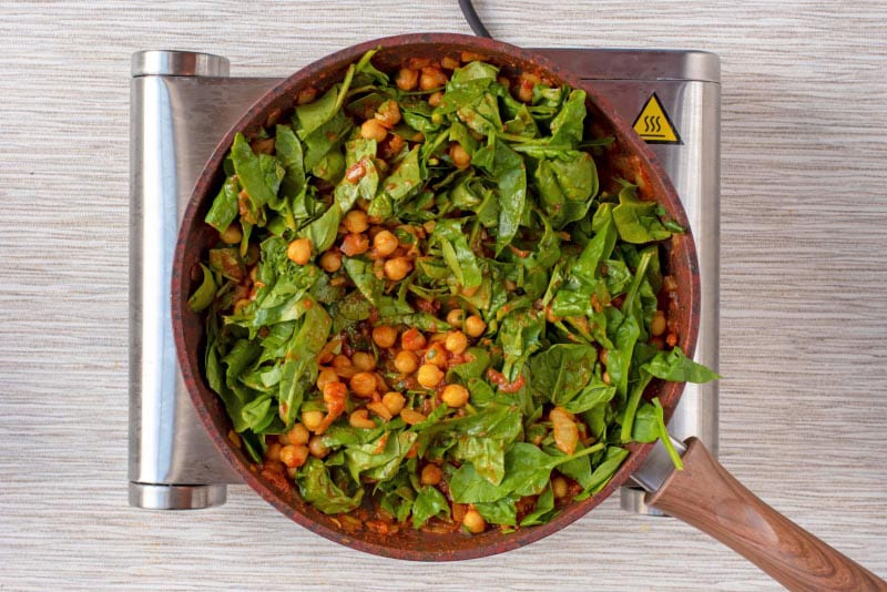Spinach, tomatoes, chickpeas, herbs and onions cooking in a frying pan