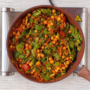 Chickpea and spinach curry cooking in a frying pan
