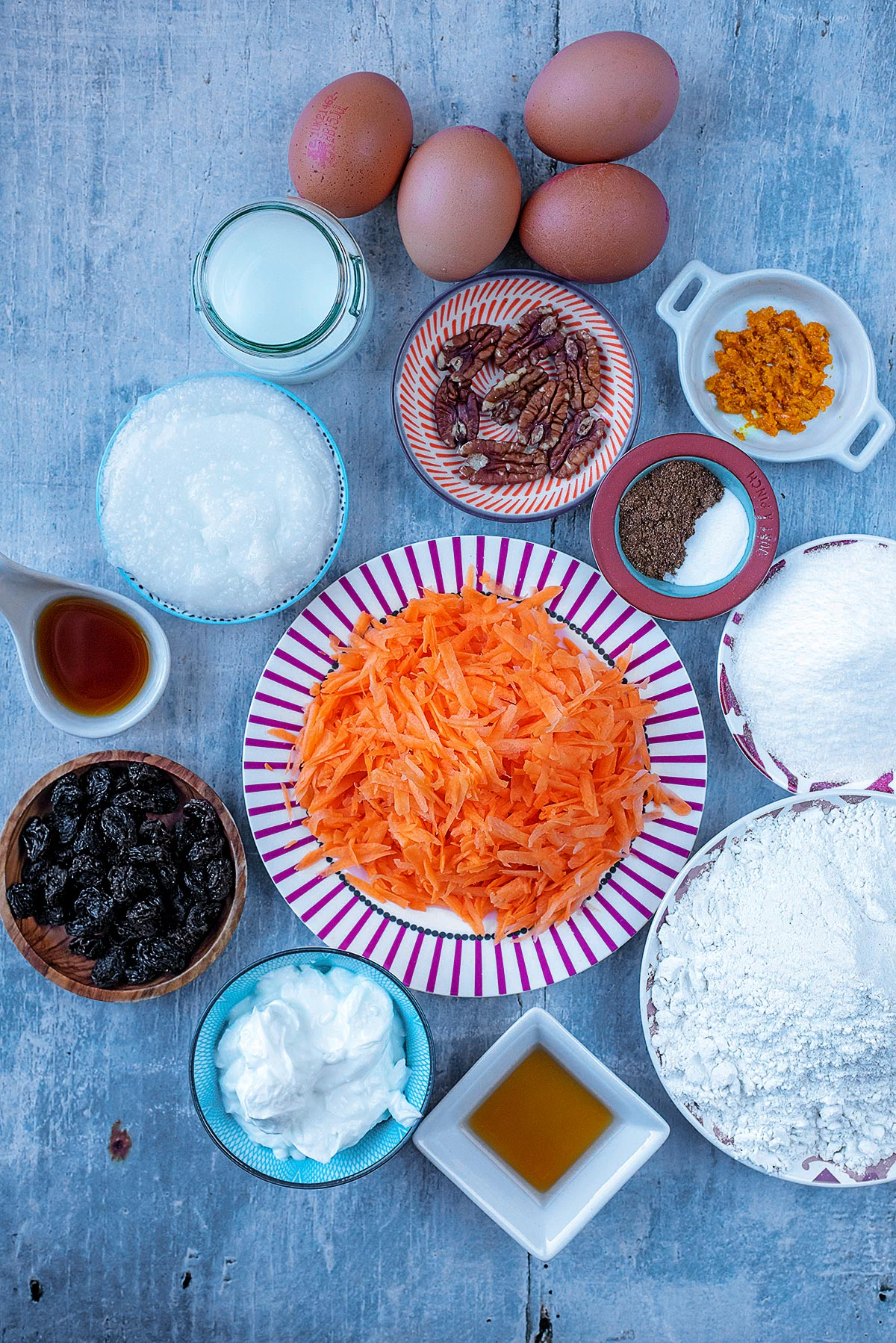 A plate of grated carrot surrounded by flour, sweetener, yogurt, raisins, nuts, spices, eggs, milk and orange zest