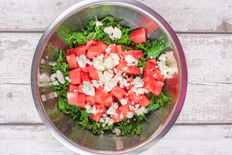 A metal bowl containing chopped raw kale, chopped watermelon and crumbled feta