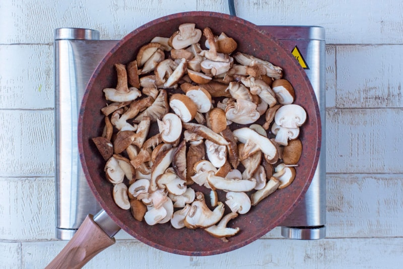 A frying pan full of sliced mushrooms