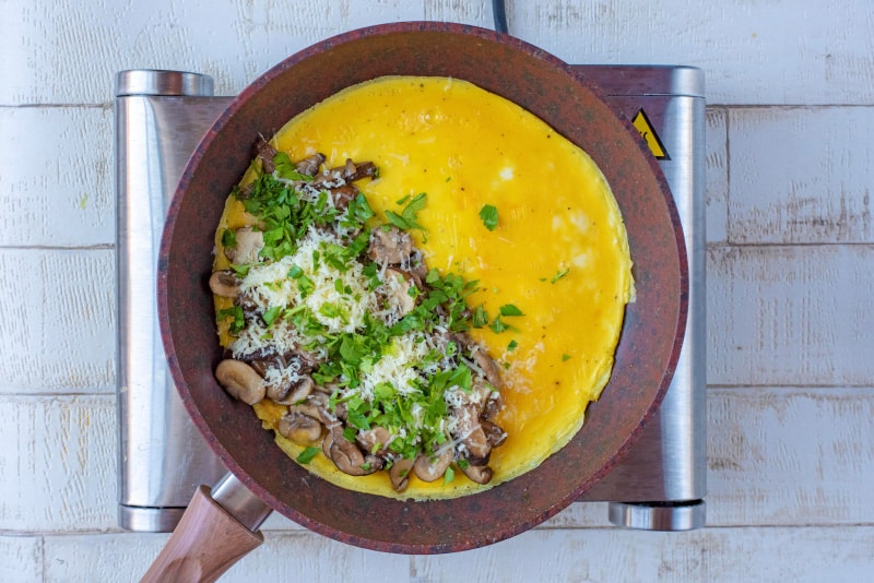A frying pan with a partially cooked omelette, half covered in mushrooms, greens and cheese