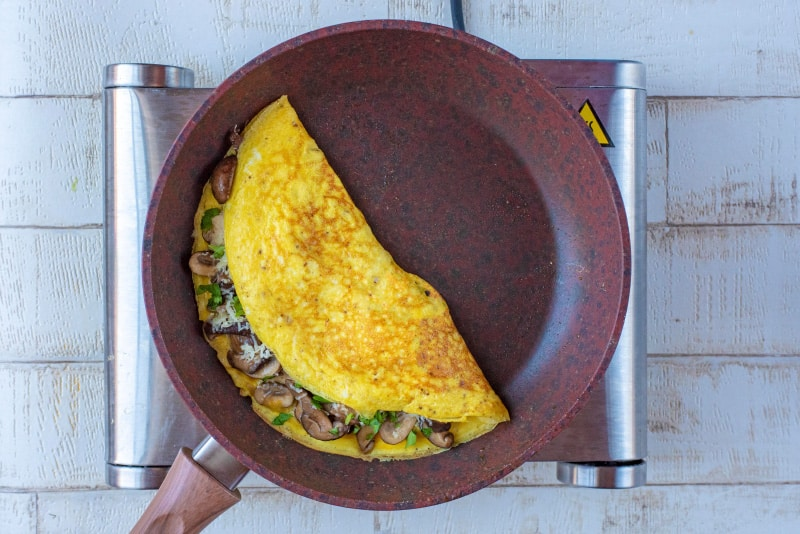 A frying pan containing a mushroom omelette folded in half