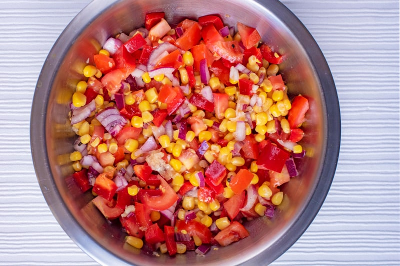 A metal bowl containing sweetcorn, red pepper, tomatoes and red onion