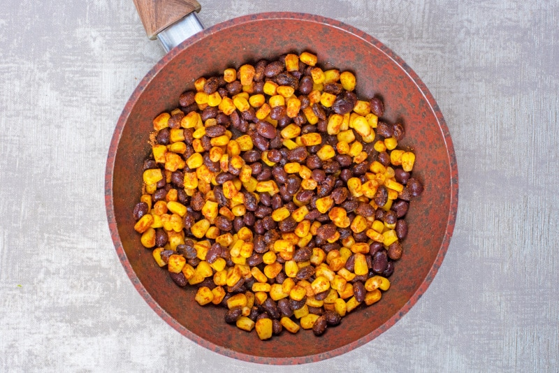 A frying pan containing sweetcorn and black beans