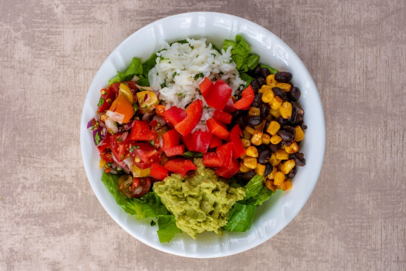 A white bowl containing shredded lettuce, rice, sweetcorn, black beans, salsa, guacamole and chopped red bell pepper