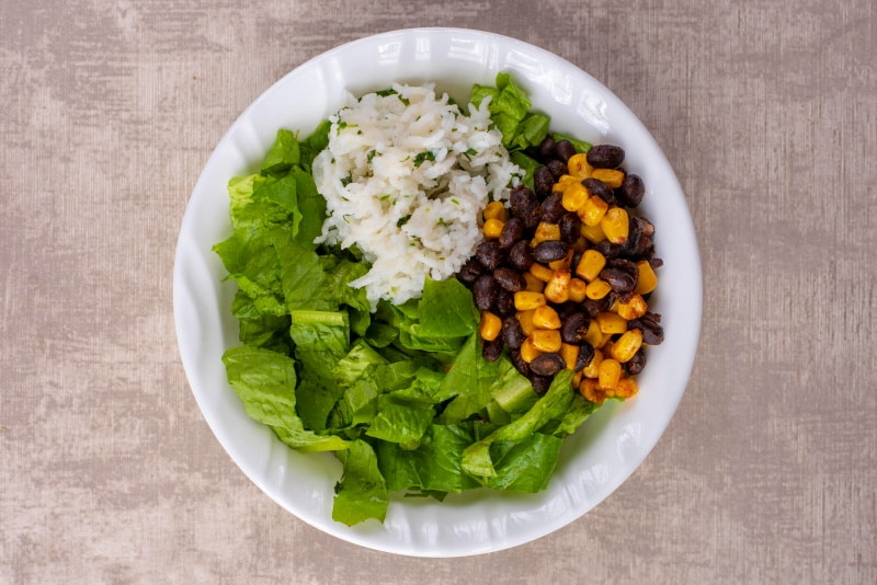A white bowl containing shredded lettuce, rice, sweetcorn and black beans