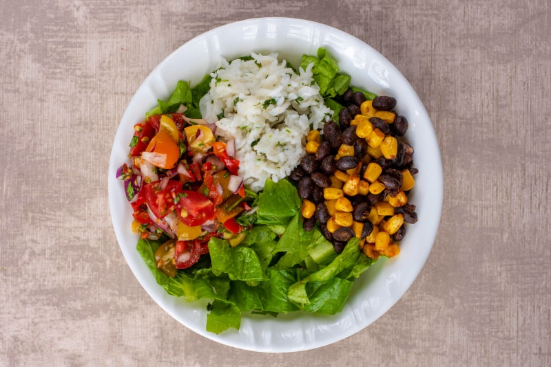 A white bowl containing shredded lettuce, rice, sweetcorn, black beans and salsa