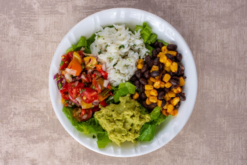 A white bowl containing shredded lettuce, rice, sweetcorn, black beans, salsa and guacamole