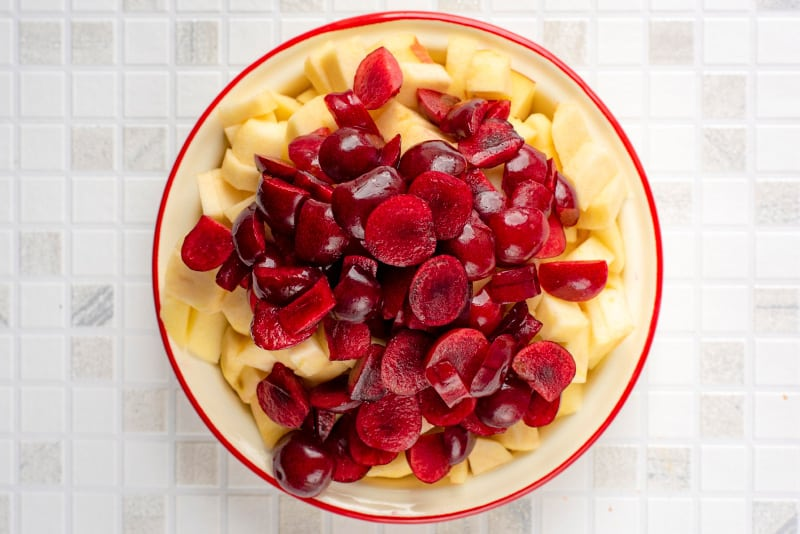 Chopped apple and cherries on a cream coloured plate