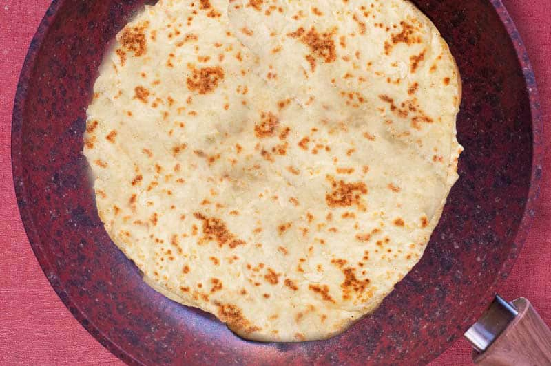 A frying pan with a cooked flatbread