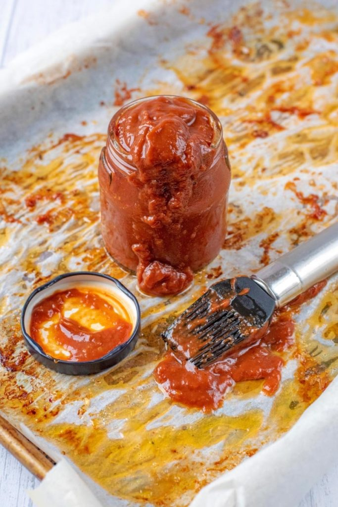 A jar of bbq sauce on a baking tray with a marinade brush