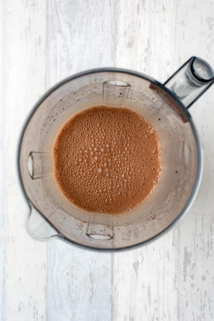 A blender jug containing a blended chocolate smoothie