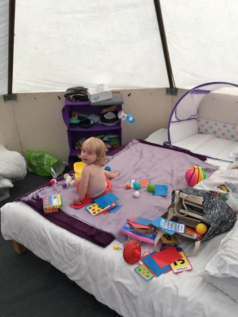 a child sat on a bed surrounded by toys