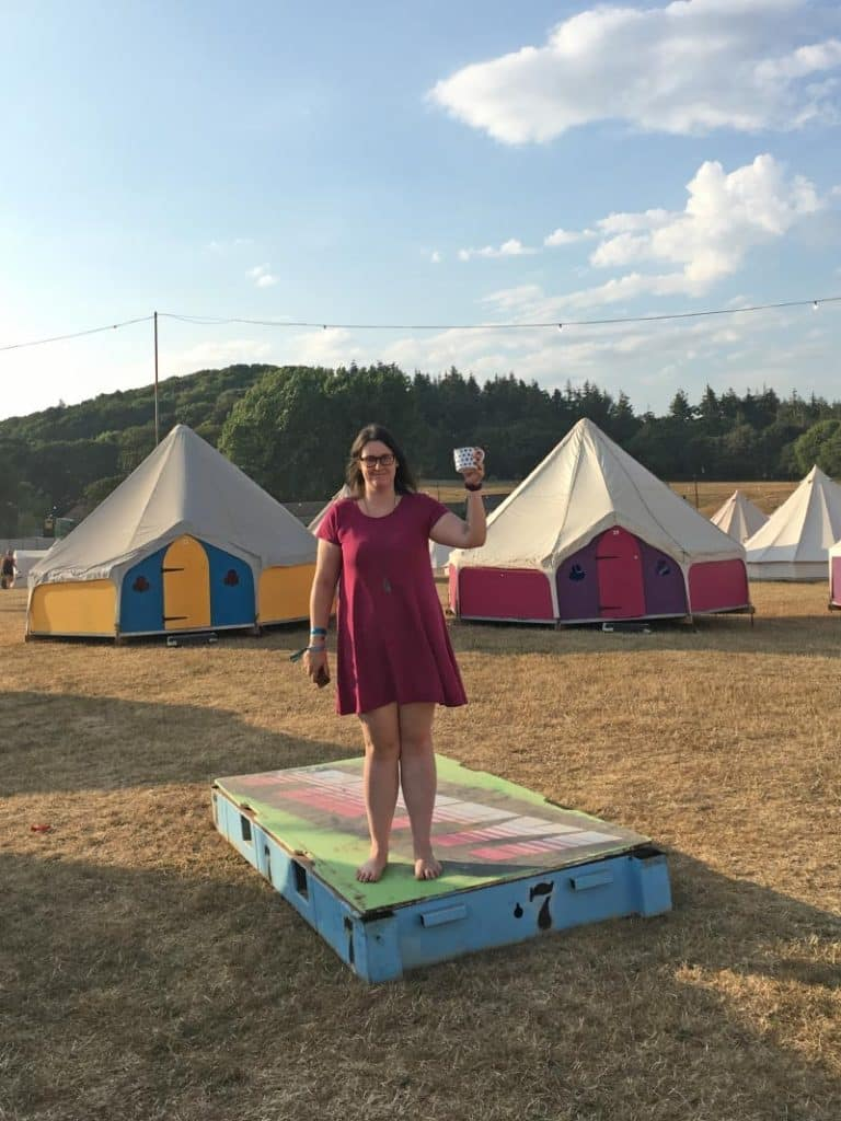a woman stood on a platform in front of colourful tents