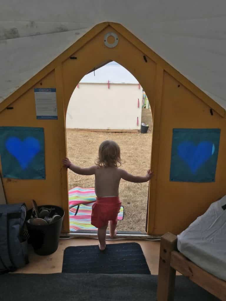 A child stood in the doorway of a tent