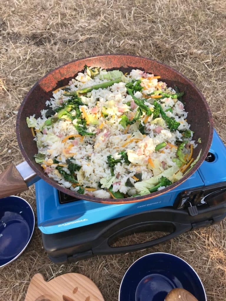 Rice and vegetables cooking in a frying pan on a camping stove