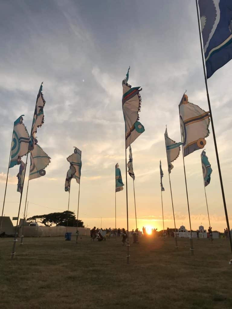 Large flags blowing in the wind as the sun sets