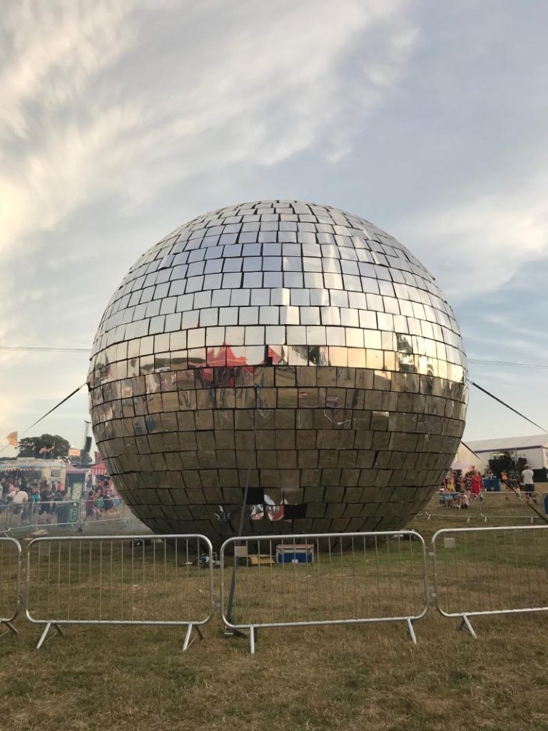 A giant disco ball surrounded by a metal fence