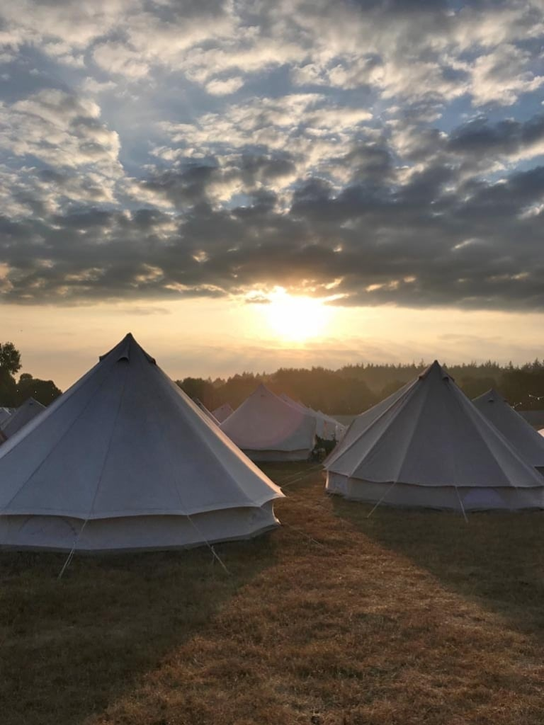 A sunrise over white tents