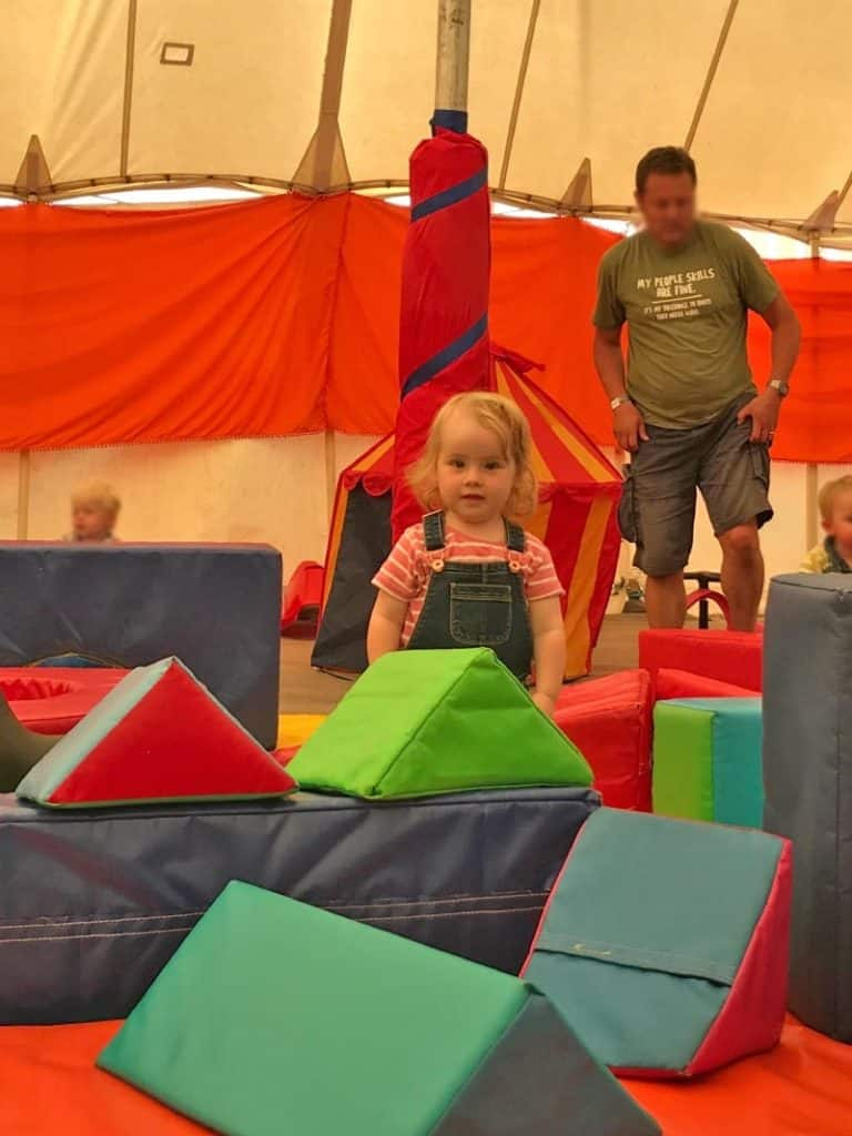 A child stood among soft play blocks