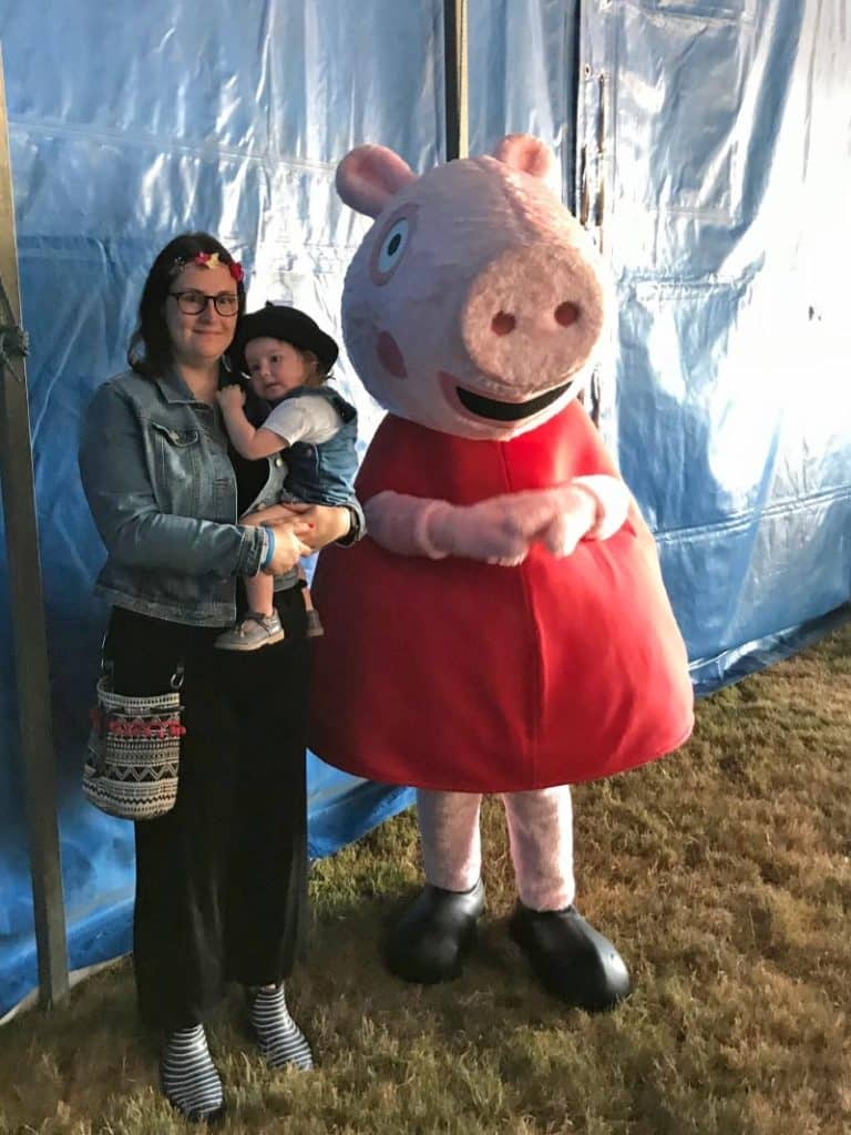 A woman holding a child next to a 6 foot Peppa Pig