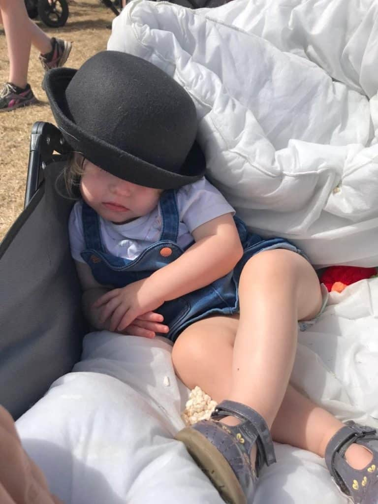 A child wearing a bowler hat asleep in a trolley