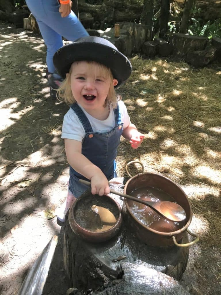A child in a hat playing with pots and pans