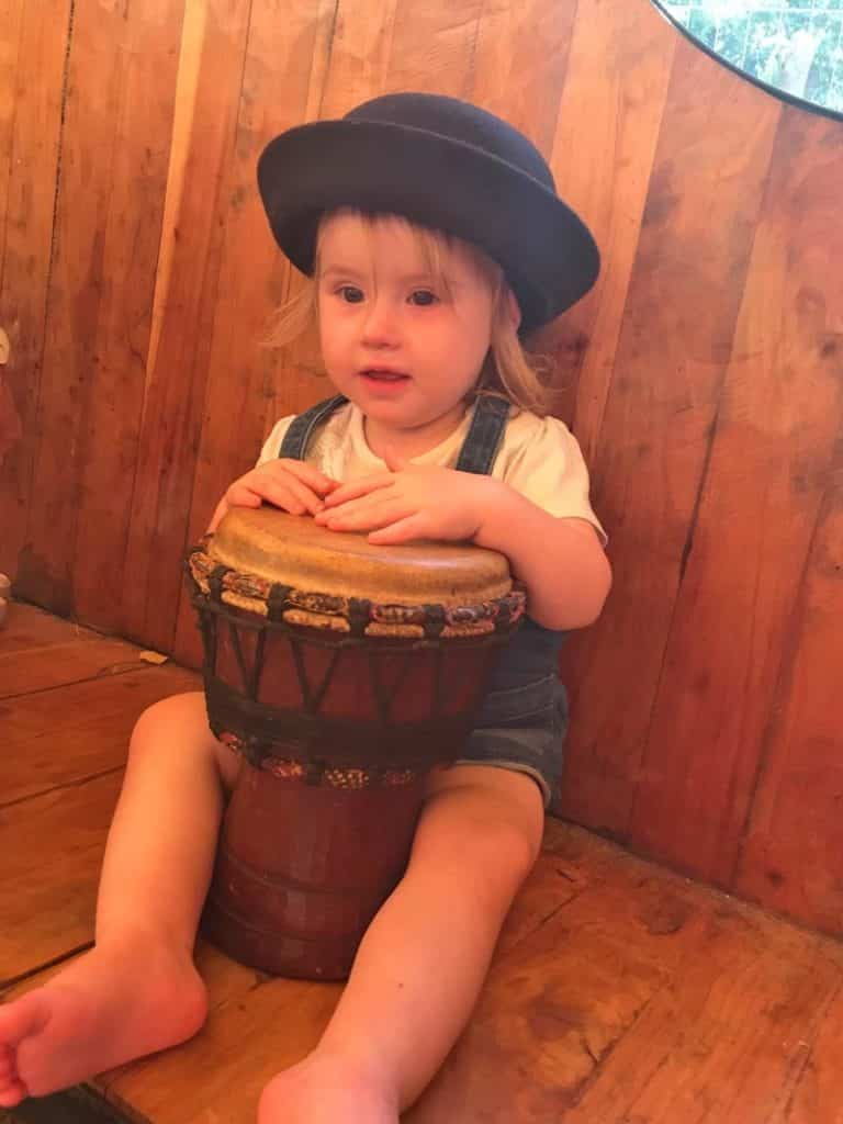 a child sat with a bongo drum
