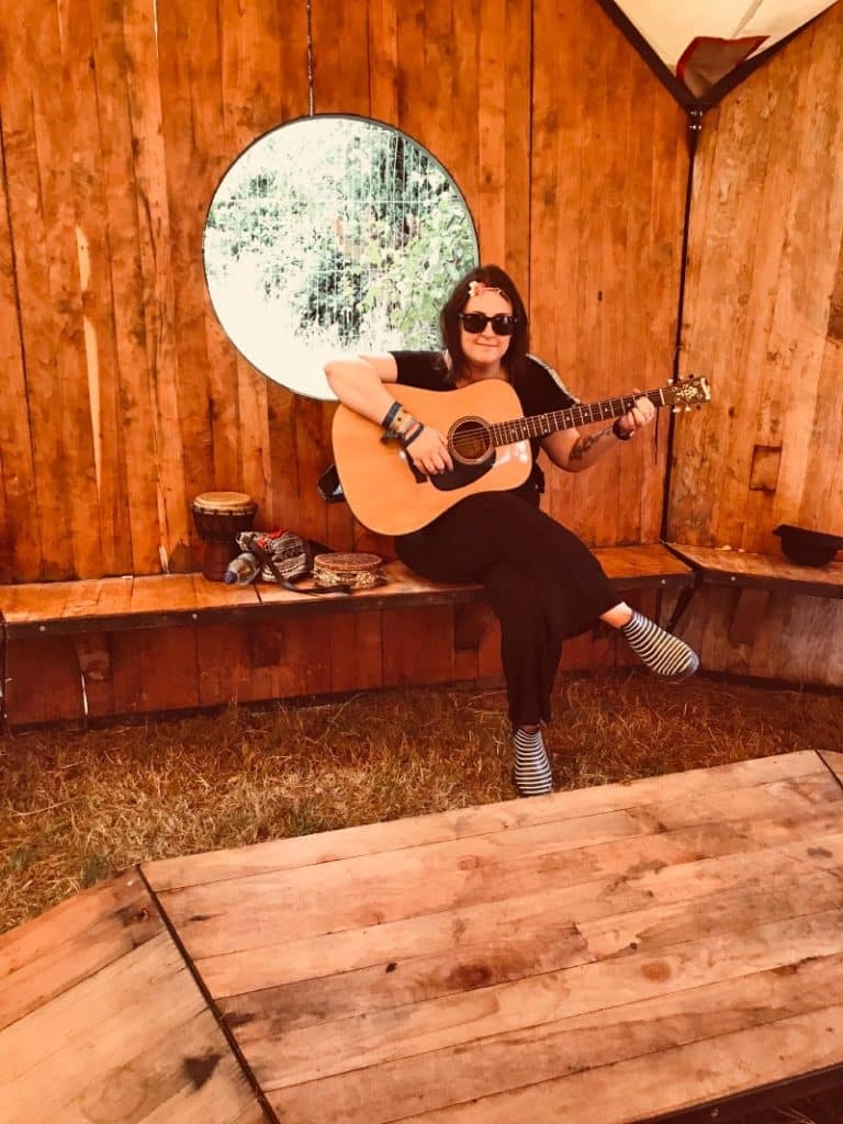 a woman sat in a wooden cabin playing guitar
