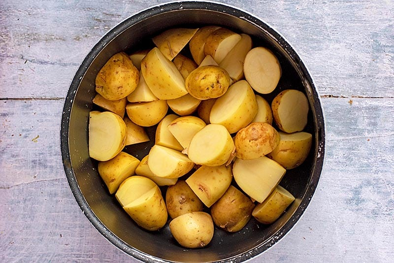 A pan full of halved new potatoes