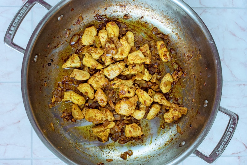 Diced chicken, chopped onions, garlic and spices cooking in a large silver pan