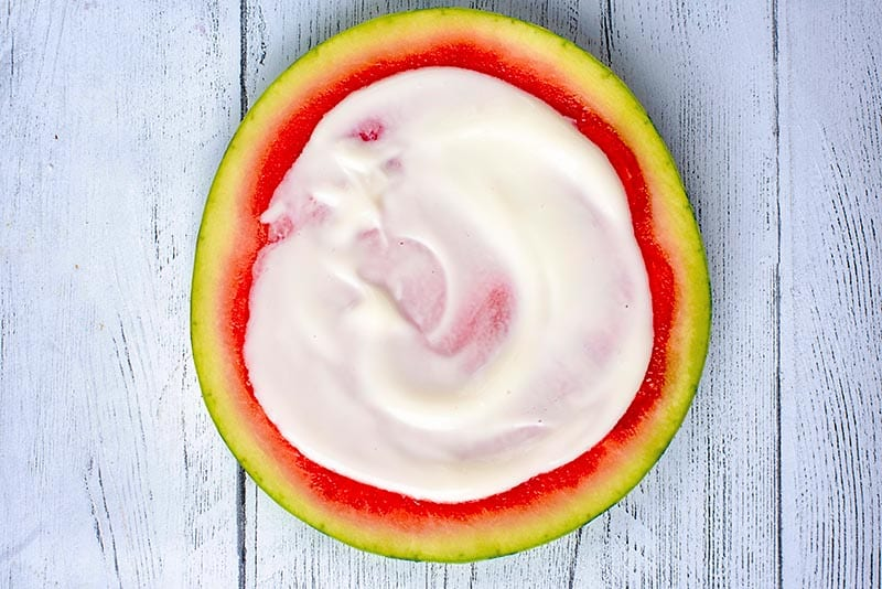 A round slice of watermelon with yogurt spread over it