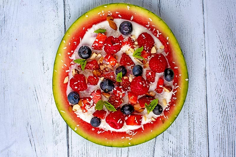 A round watermelon slice topped with yogurt, berries, crushed nuts, coconut flakes and chopped mint