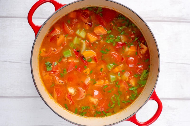 A large red pan with celery, carrots, tomatoes and stock