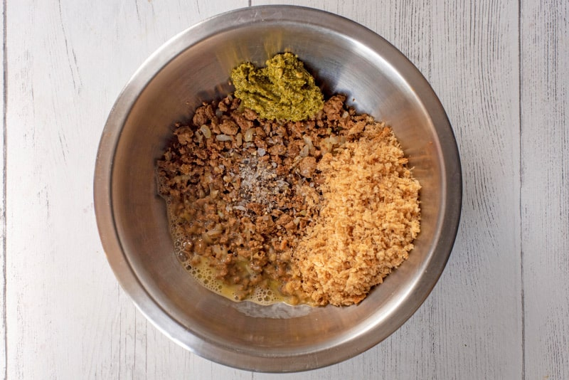 a mixing bowl containing meat free mince, onion, breadcrumbs and pesto