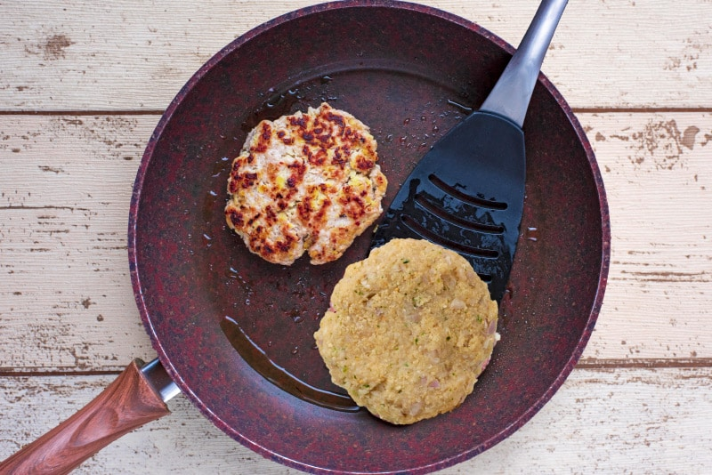 Two chicken burger patties in a frying pan, one has been flipped to show the cooked side