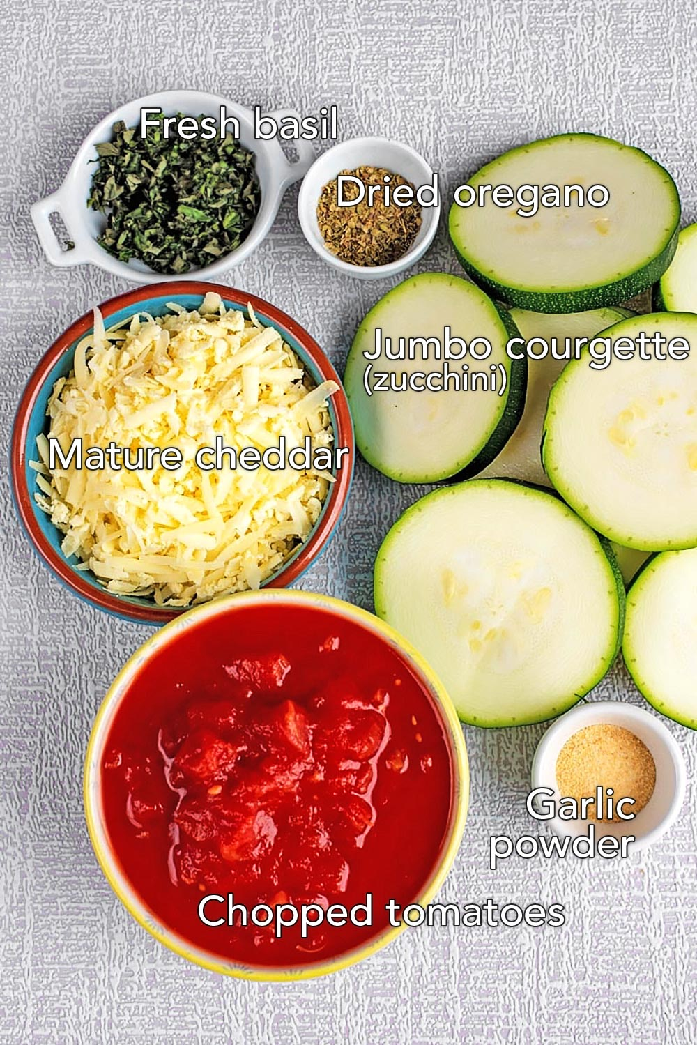 Sliced courgette (zucchini), a bowl of tomatoes, grated cheese and herbs on a textured surface